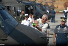 A Philippine Air Force chaplain blesses a newly-delivered Bell 412 helicopter with holy water during a christening ceremony in Manila on August 17, 2015