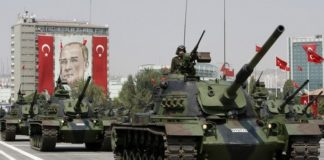 Turkish army tanks roll past a portrait of Mustafa Kemal Ataturk during a military parade in Ankara