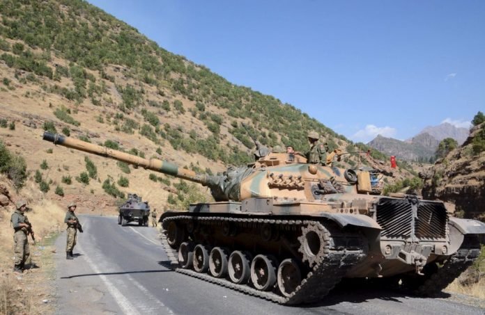 Turkish soldiers in a tank and an armored vehicle patrol on the road to the town of Beytussebab in the southeastern Sirnak province, Turkey